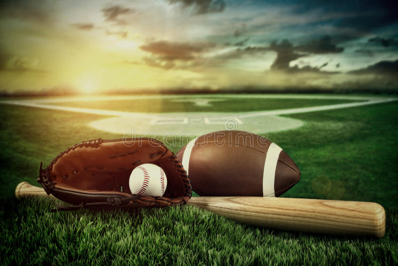 棒球、在域的棒和露指手套在日落 免版税库存照片