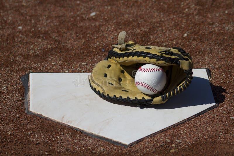 棒球有球的俘获器露指手套在Homeplate 免版税库存图片