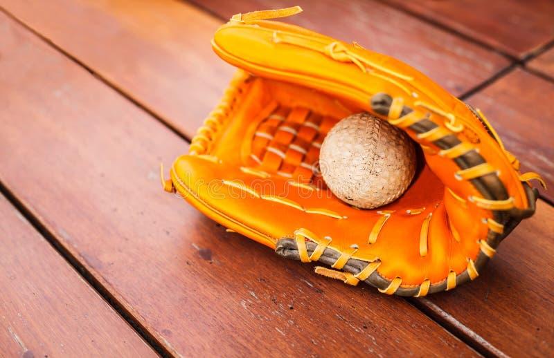 棒球,与皮革露指手套手套的垒球在与拷贝空间的木桌地板背景 体育休闲题材 免版税图库摄影