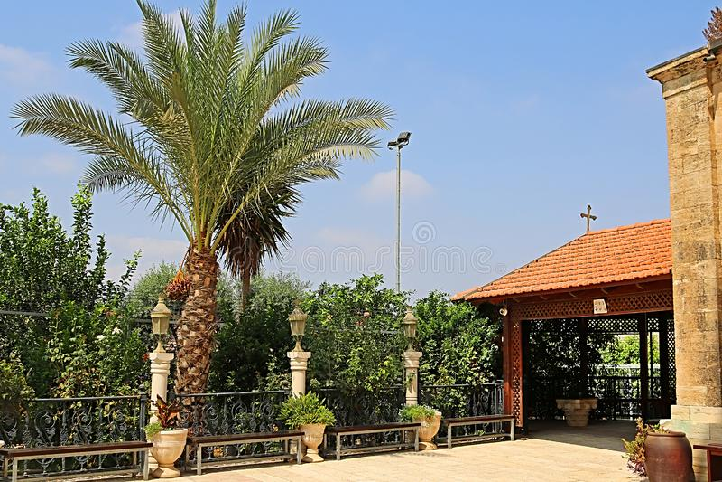 棕榈和树荫处在卡纳东正教婚姻的教会的围场在内盖夫加利利,Kfar Kana的卡纳 免版税库存图片