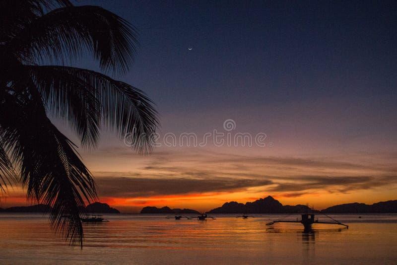 棕榈树和小船剪影在明亮的日落天空背景 在热带海滩的风景日落与在背景的山 图库摄影