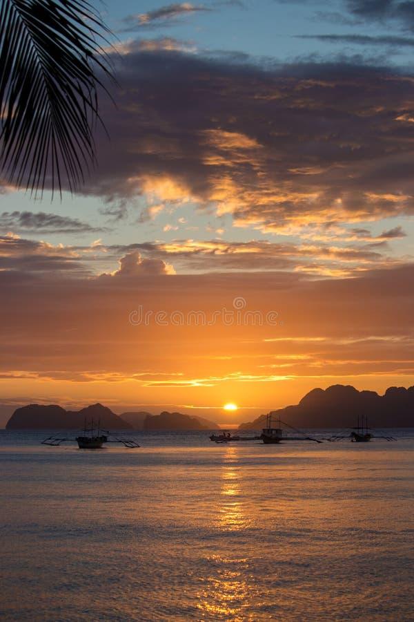 棕榈树和小船剪影在明亮的日落天空背景 在热带海滩的风景日落与在背景的山 免版税库存照片