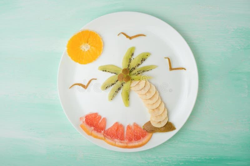棕榈树和果子太阳,创造性在一块白色板材的食物 在倾吐的餐馆沙拉的主厨概念食物新鲜的厨房油橄榄 库存图片