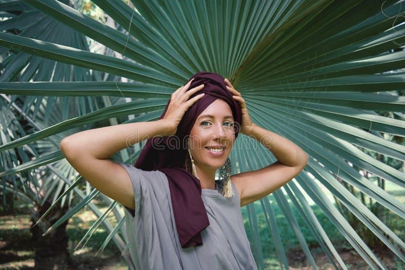 棕榈树背景的妇女  免版税图库摄影