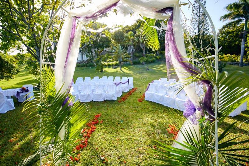 棕榈被装饰的婚姻的曲拱在有凤凰木的豪华的热带庭院里 库存图片