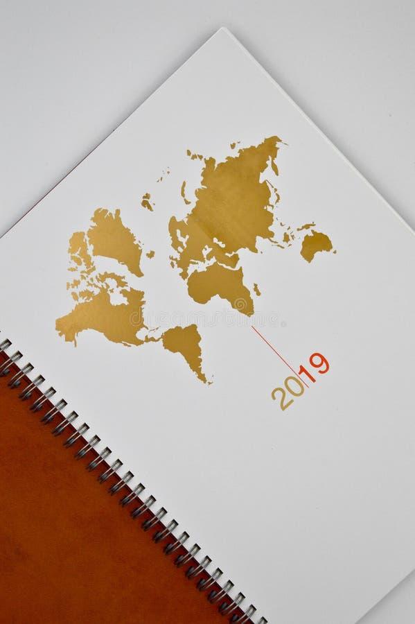 2019棕色皮革议程和世界地图 免版税库存图片