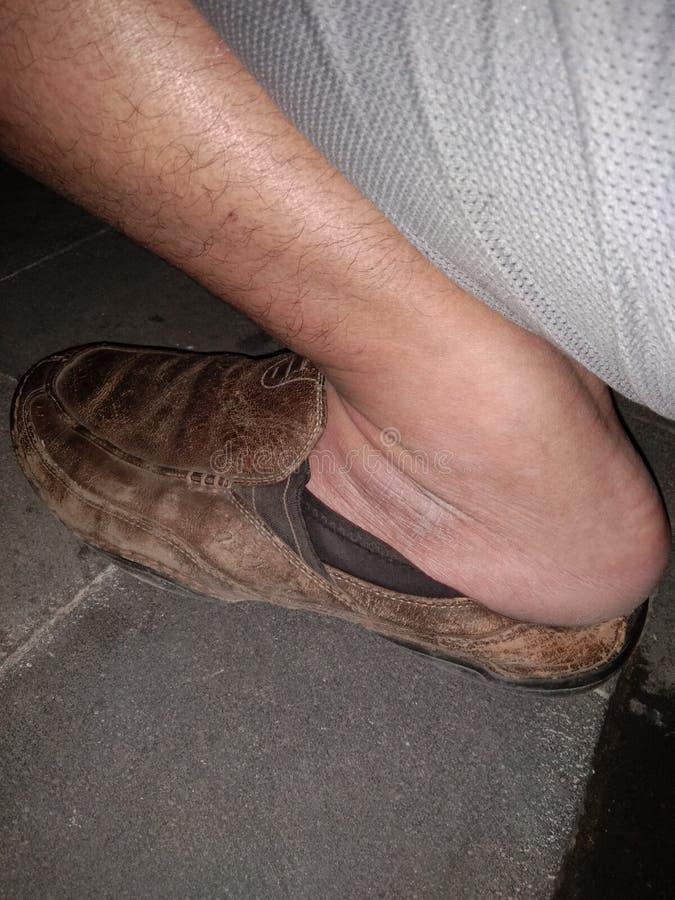 棕色皮鞋出现在左脚 免版税库存图片