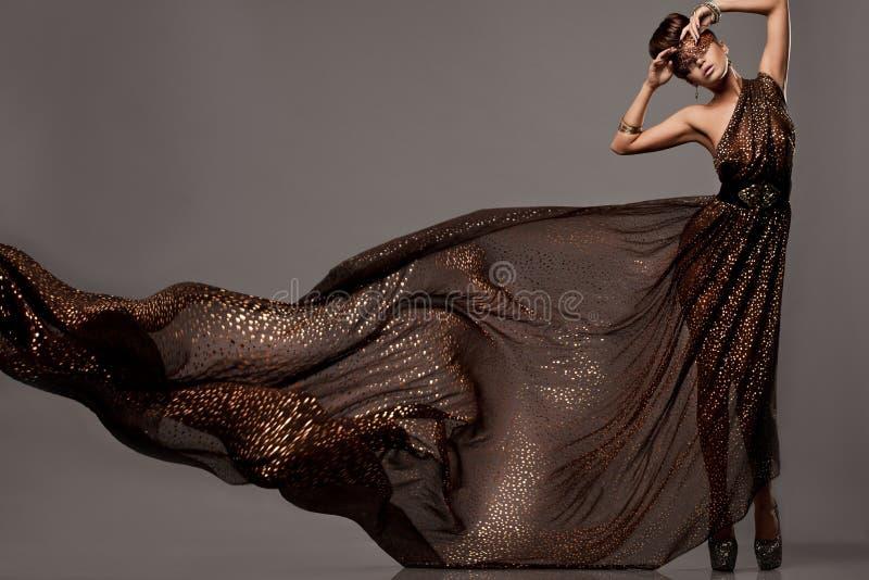 棕色礼服的妇女 免版税图库摄影