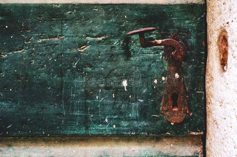 棕色金属把柄用在老绿色门的铁锈盖 古色古香称呼 r ?? 图库摄影