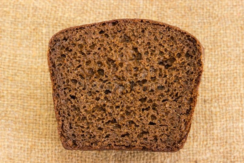 棕色黑麦和麦子面包裁减看法在麻袋布的 免版税库存图片