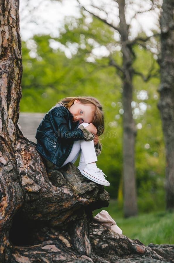 森林公园树干上长发小女孩像 图库摄影