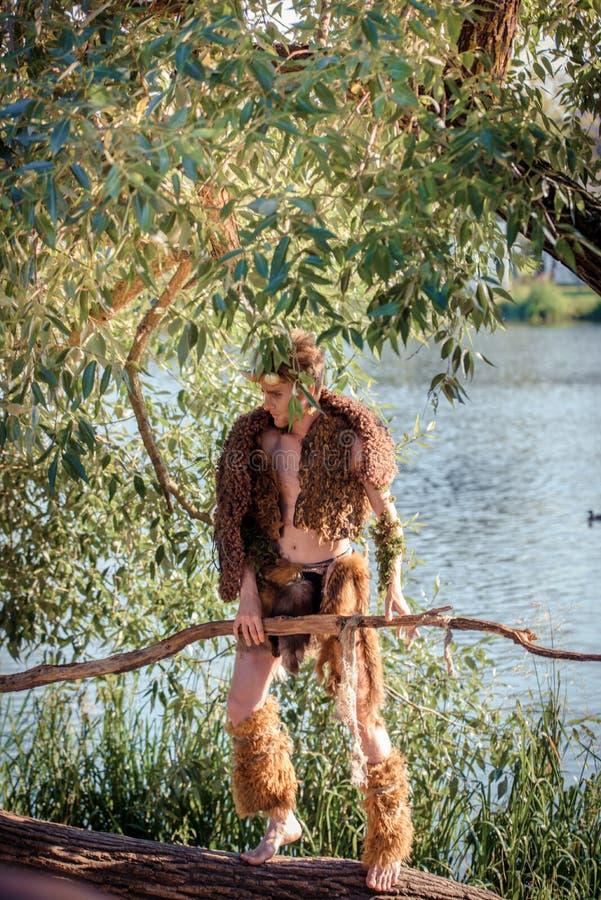 森林国王 百兽之王在毛皮的 野生年轻人 垫铁和构成 对chelowin的时尚概念 河森林和太阳 免版税库存图片