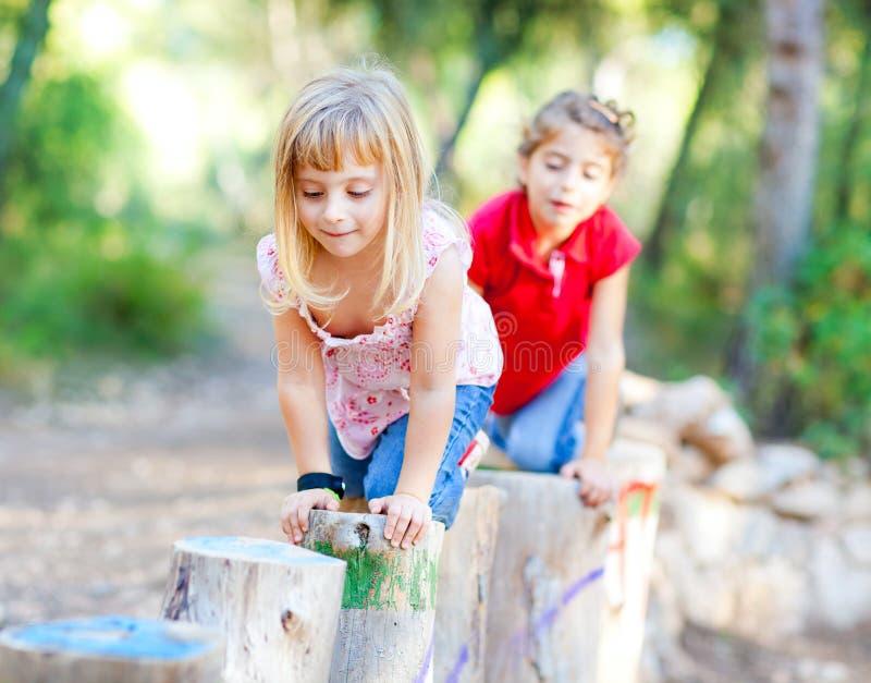 森林女孩演奏树干的孩子本质 免版税库存照片