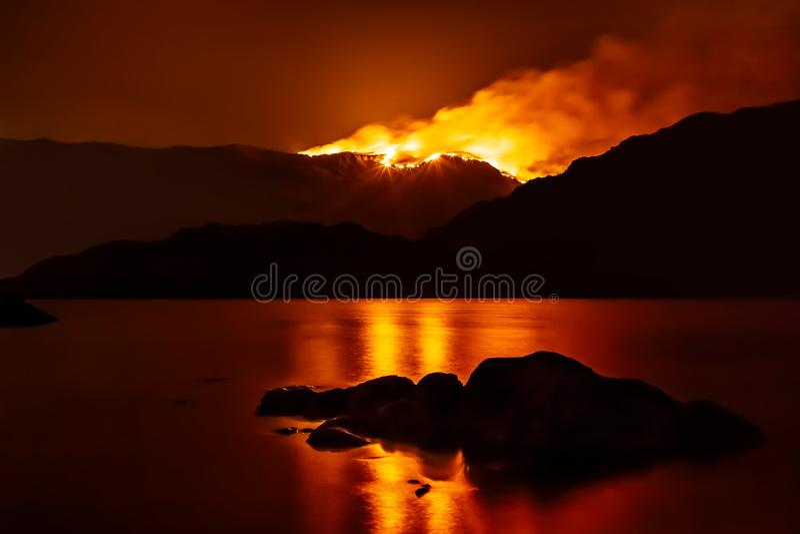 森林火灾在反射在附近的湖的晚上 免版税库存图片