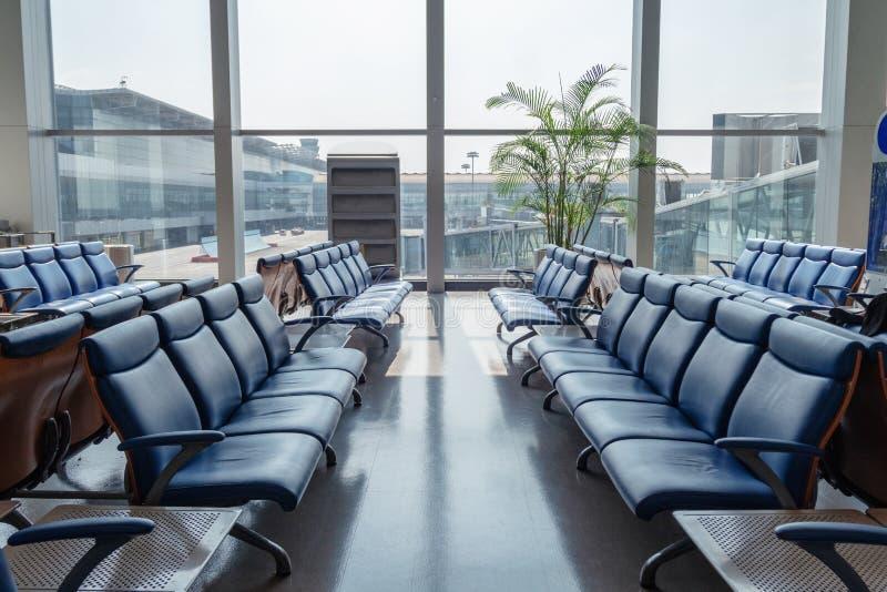 椅子与玻璃窗的在终端发光在机场 免版税库存照片