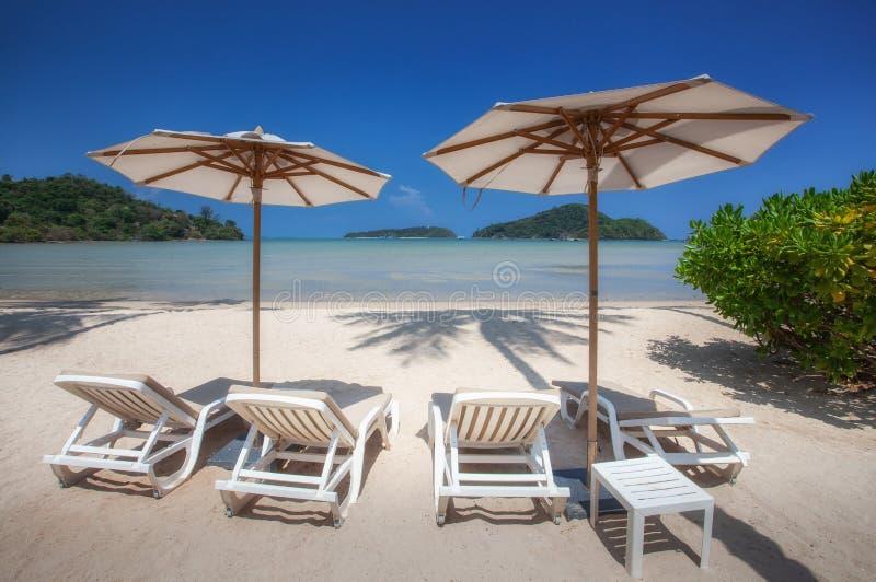 椅子和伞在热带沙滩 免版税库存照片