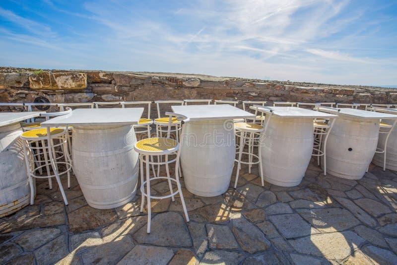椅子和白色桌由葡萄酒桶,一家室外餐馆做成 库存图片
