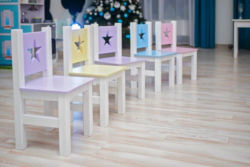 椅子在儿童房间 哄骗室内部 椅子在幼儿园学龄前教室 许多明亮地色的椅子为 免版税库存照片