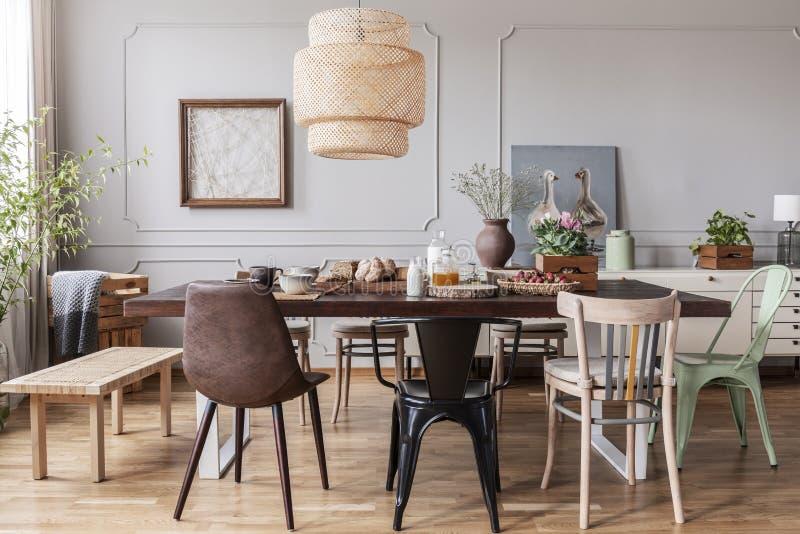 椅子在灯下的木餐桌上在与海报和花的餐厅内部 实际照片 免版税库存照片