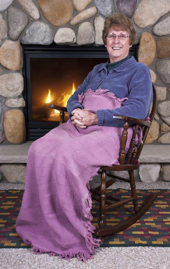 椅子晃动高级妇女的壁炉祖母 免版税库存照片