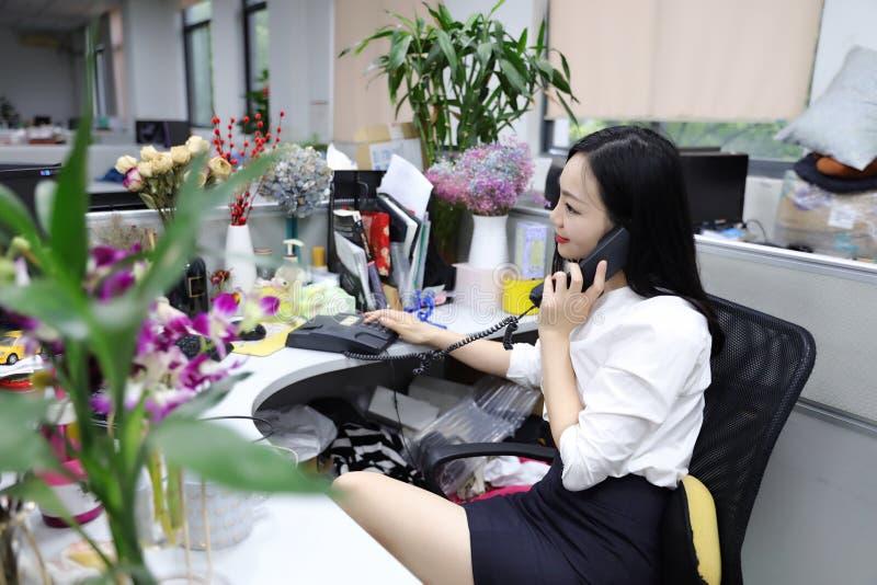 椅子的亚洲中国办公室夫人妇女女孩做一张电话用途书桌给闲谈工作微笑穿戴企业职业衣服工作场所打电话 免版税库存图片
