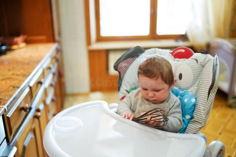 椅子的婴孩在厨房里 童年的概念 免版税库存照片