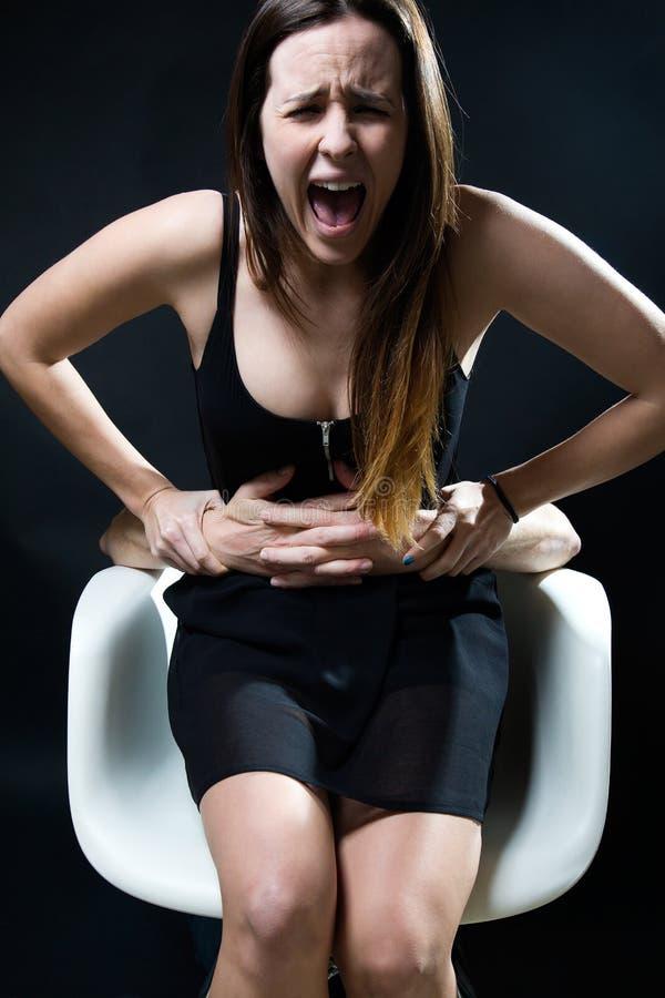 椅子的少妇由捉住了男性胳膊 概念压迫 库存照片