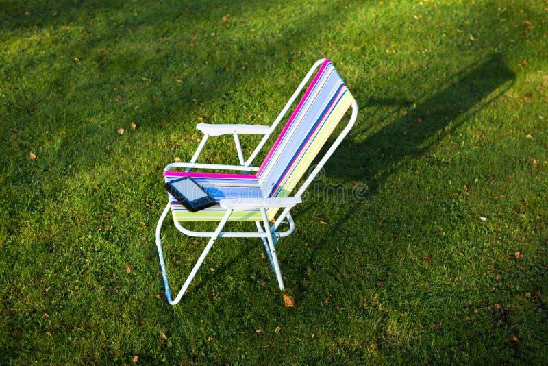 椅子的E书读者 图库摄影