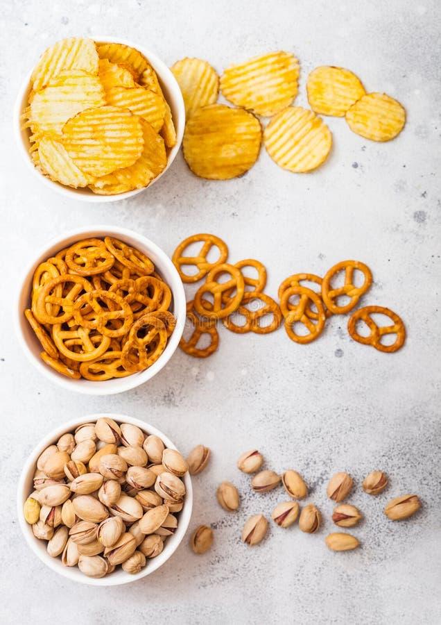 椒盐脆饼和油炸薯片和开心果在白色陶瓷碗在石厨房用桌背景 啤酒的快餐 免版税库存照片