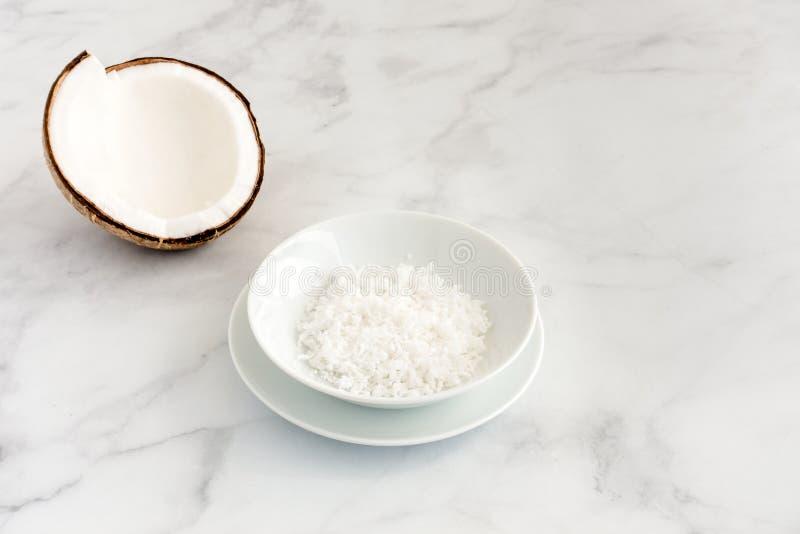 椰子一半和被磨碎的椰子在一个碗在白色大理石 库存图片