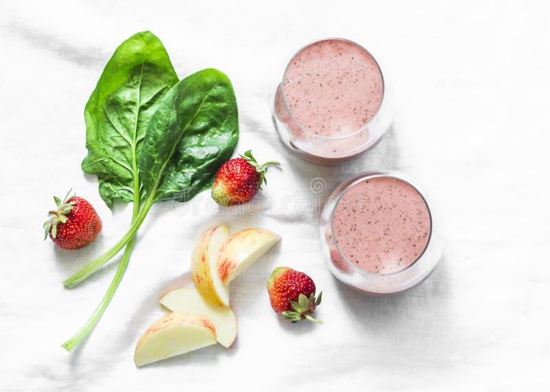 椰子前生命期的酸奶,菠菜,苹果,草莓在轻的背景的戒毒所圆滑的人,顶视图 健康饮食食物概念 库存照片