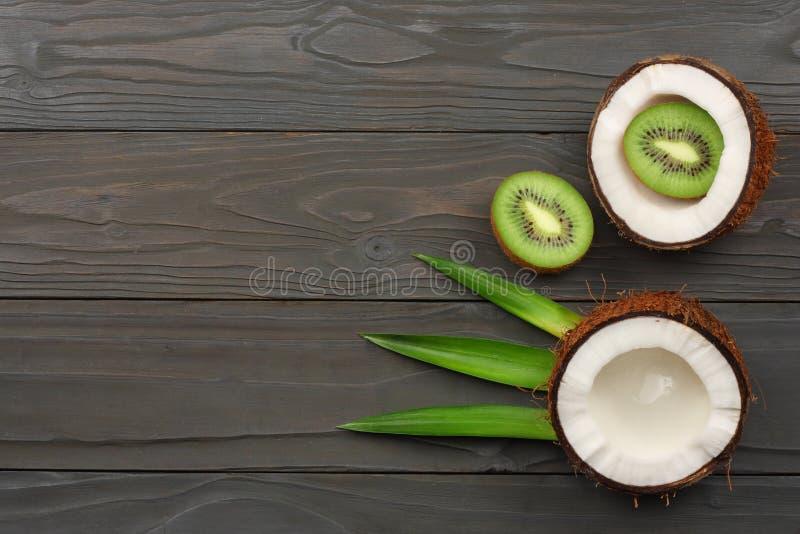 椰子用猕猴桃和绿色在黑暗的木背景离开 与拷贝空间的顶视图 图库摄影