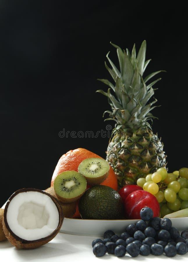 从椰子,菠萝,成熟的各种各样的新鲜水果,苹果和葡萄在白色桌上在黑背景中健康的 库存图片