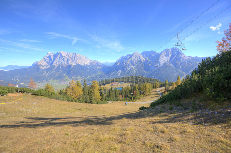 楚格峰和Sonnenspitze全景在与Ehrwald村庄的一个晴天山的脚的 免版税库存图片
