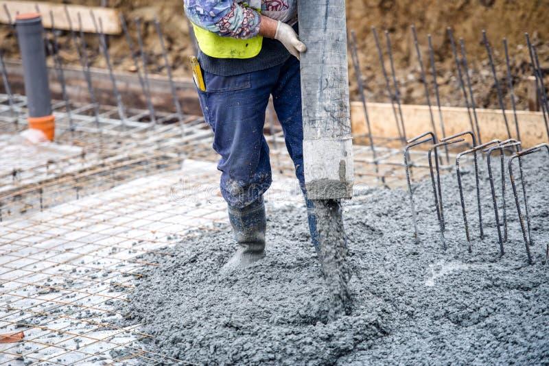 楼房建筑工作者倾吐的水泥或混凝土与泵浦管 免版税库存照片