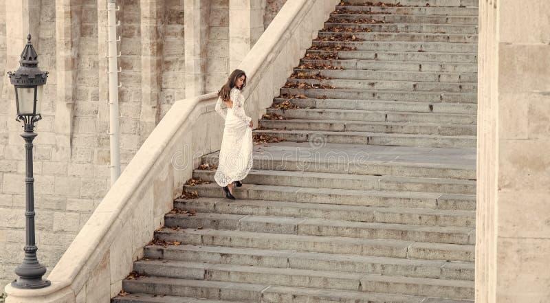 楼梯的肉欲的妇女 白色婚礼礼服的,时尚妇女新娘 有魅力神色的女孩 与长期的时装模特儿 免版税库存图片