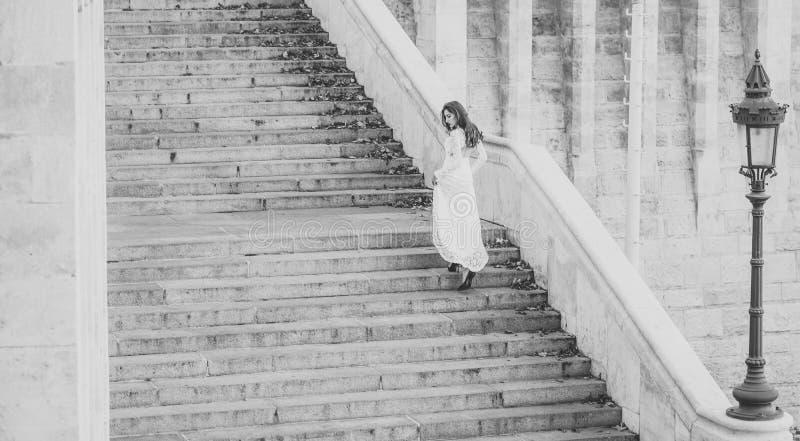 楼梯的肉欲的妇女 白色婚礼礼服的,时尚妇女新娘 有魅力神色的女孩 与长期的时装模特儿 免版税图库摄影