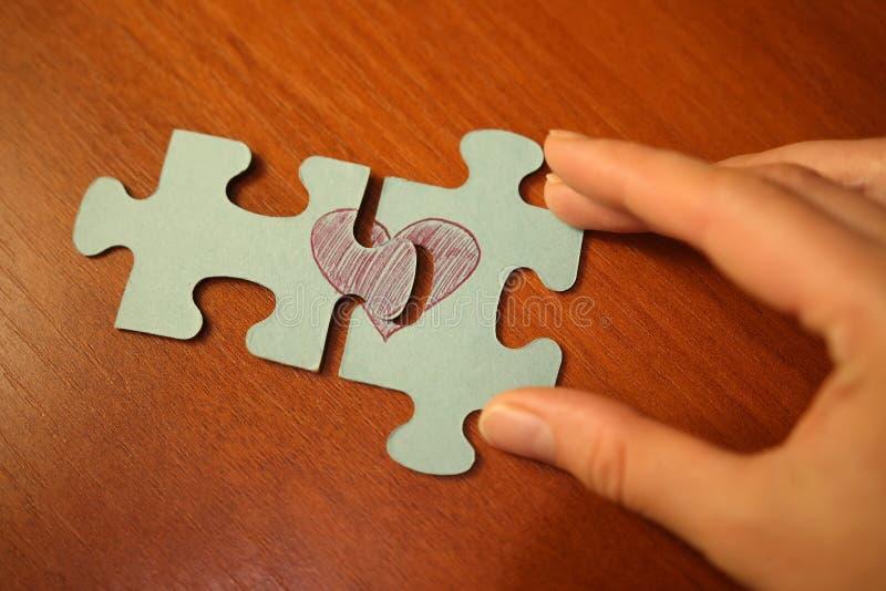 概念亲吻妇女的爱人 手折叠与红色心脏的图片的难题 心脏零件难题  免版税库存照片