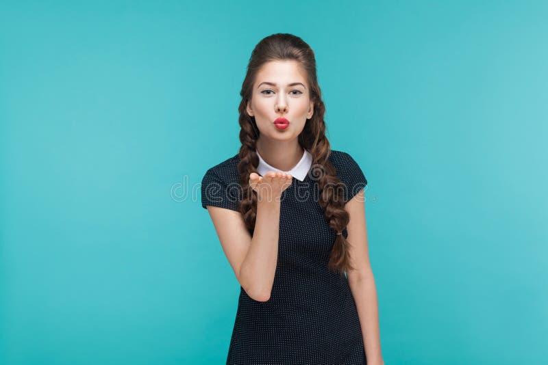 概念亲吻妇女的爱人 美丽的可爱的妇女送空气亲吻在照相机 库存照片