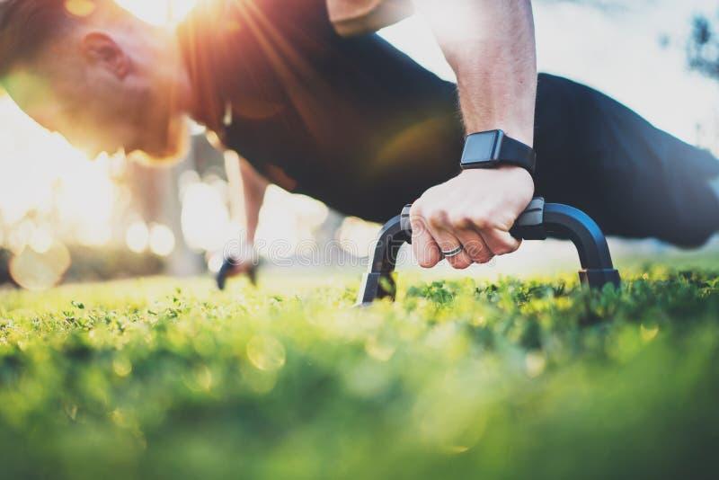 概念健康生活方式 户外培训 做俯卧撑的英俊的体育人在公园在晴朗的早晨 蠢材 免版税库存照片