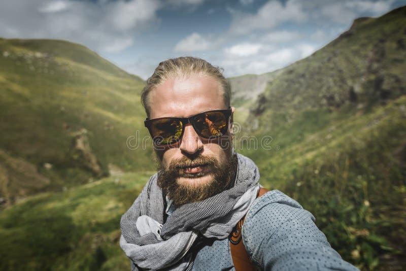 概念全球旅行 太阳镜的年轻步行的人采取在山风景的背景的Selfie 免版税库存照片
