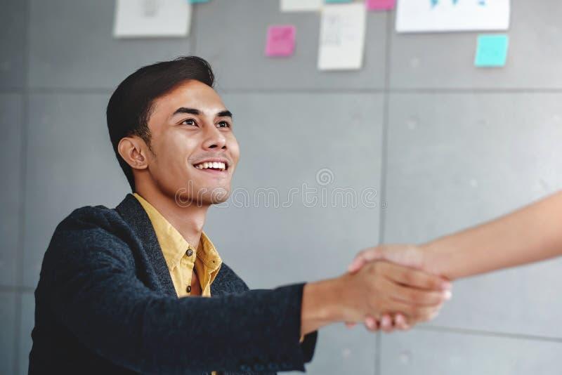 概念另外现有量合伙企业编结难题二 在办公室候选会议地点握手的愉快的年轻商人 库存照片