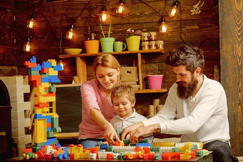 概念建筑手指金子安置关键字 有母亲和父亲戏剧的小孩与玩具建筑集合 家庭修造结构模型 免版税库存照片