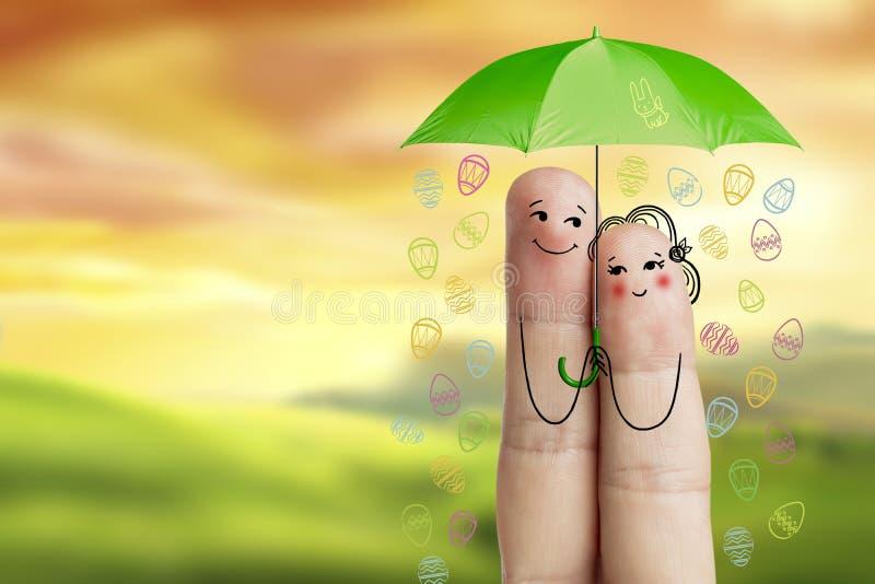 概念性复活节手指艺术 夫妇拿着绿色伞用落的复活节彩蛋 图象纵向股票妇女年轻人 免版税图库摄影