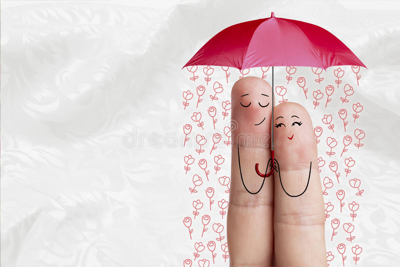 概念性手指艺术 恋人是拥抱和拿着有落的花的伞 图象纵向股票妇女年轻人 库存图片