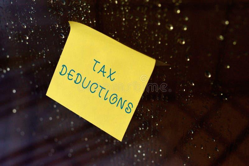 概念性手文字陈列税收减免 企业照片文本从某人减去s的数额或费用是 免版税图库摄影