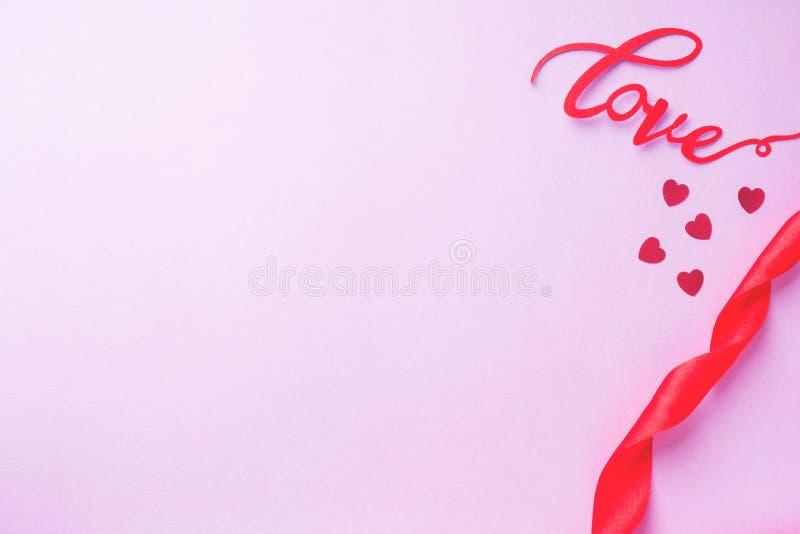 概念情人节、红色丝带和题字爱在桃红色背景 库存图片