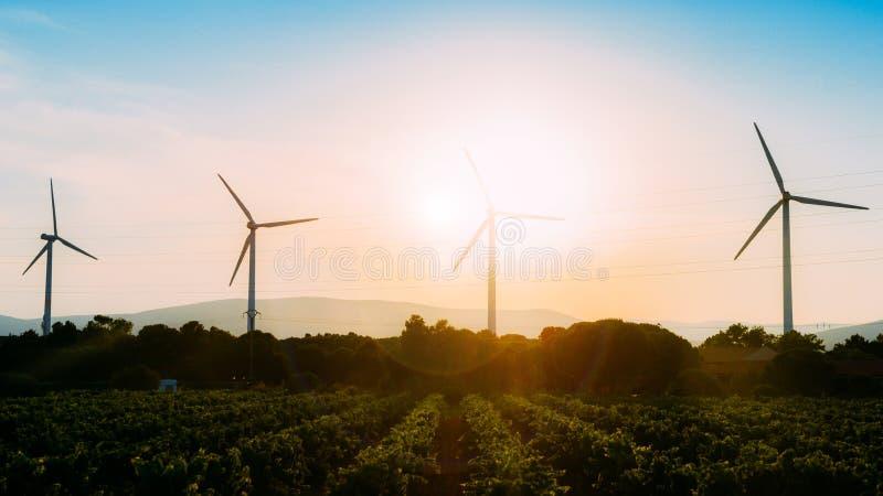 概念想法eco力量能量 在小山的风轮机与日落 免版税库存图片