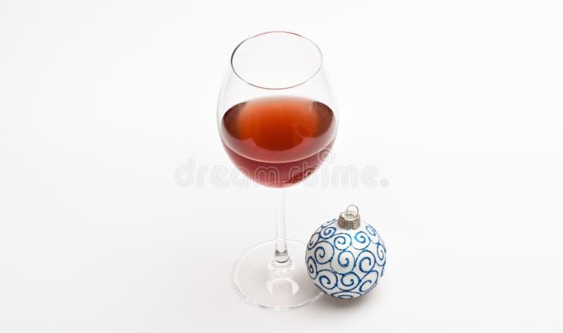 概念新的当事人年 有在白色背景隔绝的红色液体或酒和圣诞节球装饰品的葡萄酒杯 库存照片