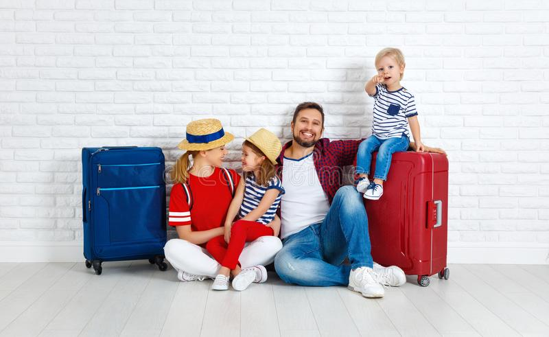 概念旅行和旅游业 带着手提箱的愉快的家庭临近w 免版税库存照片